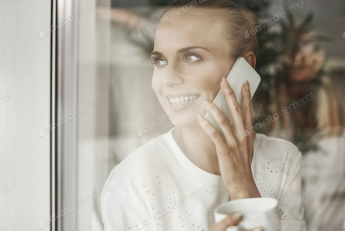Happy businesswoman looking through window and talking by mobie phone