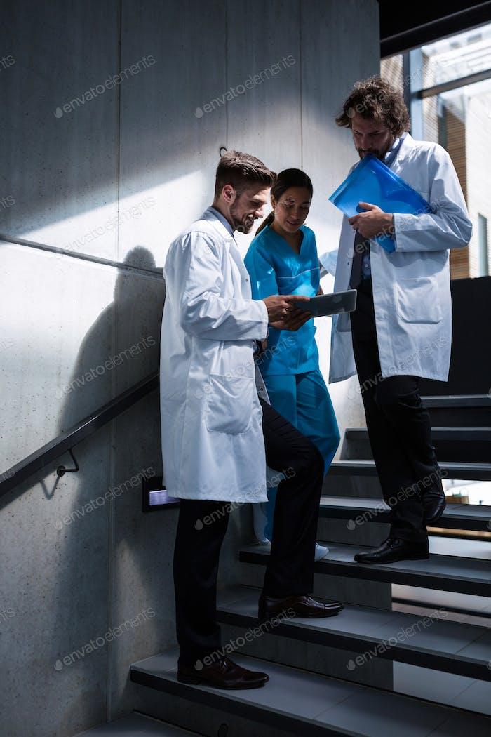 Doctors and nurse looking at digital tablet