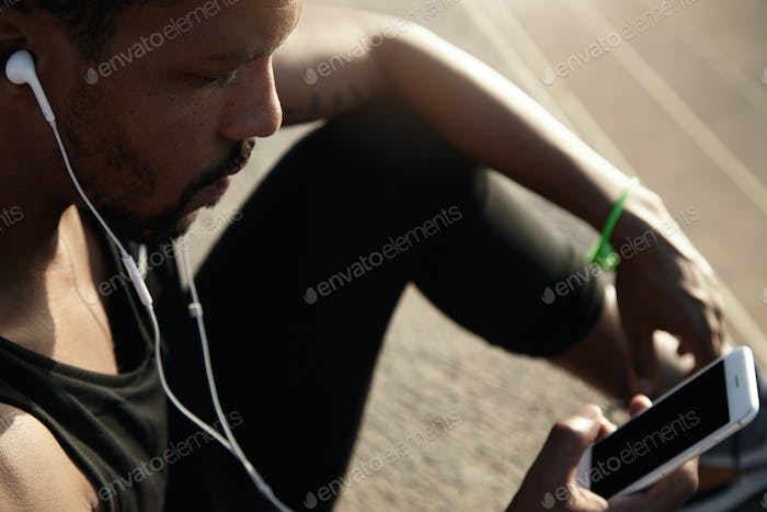 Human and technology concept. People and sport. Handsome African guy in headphones listening to musi