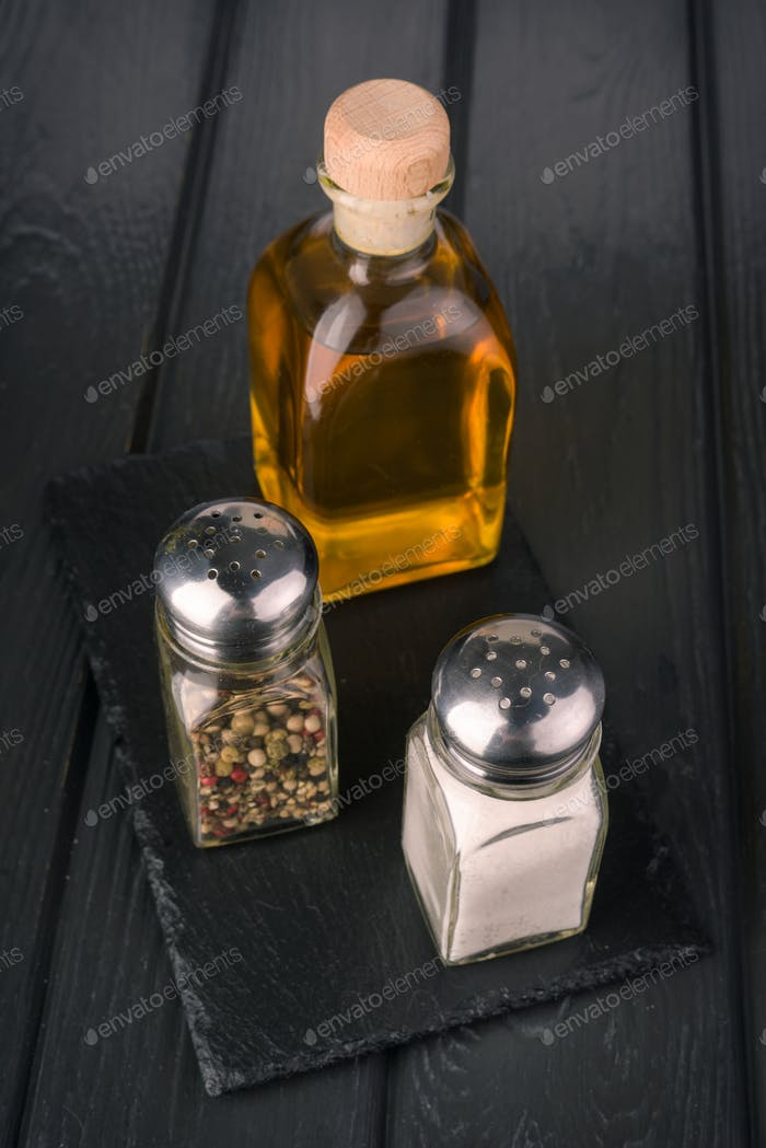 condiments for salad on black wooden board