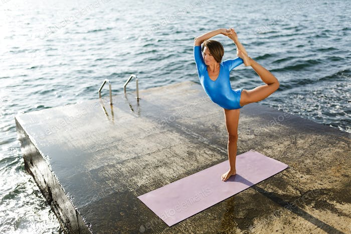 Thoughtful woman standing and training yoga poses while dreamily looking aside by the sea