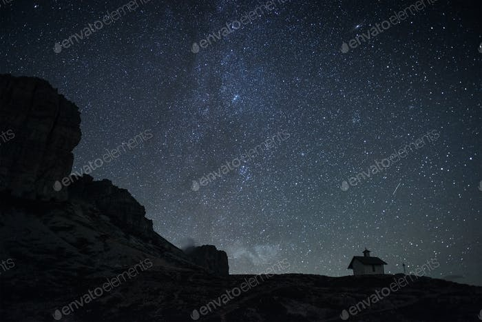 Milky way on the horizon. View from mountain with small building on it