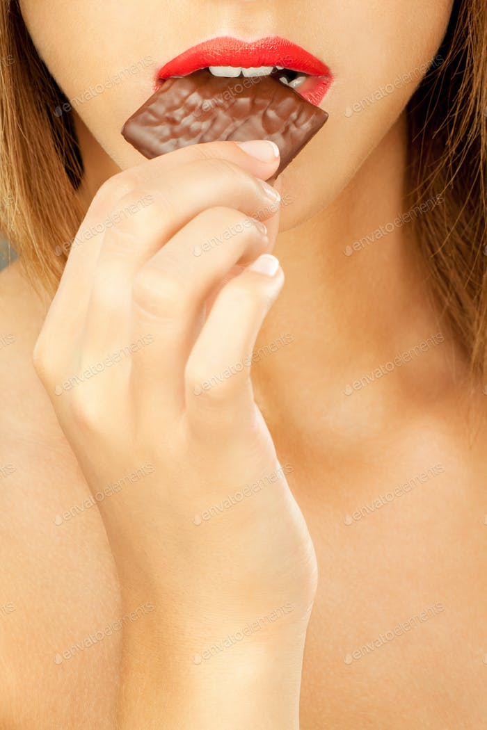 woman bitting chocolate bar