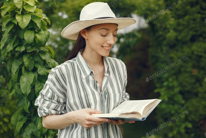 Woman in a hat with a book in a garden