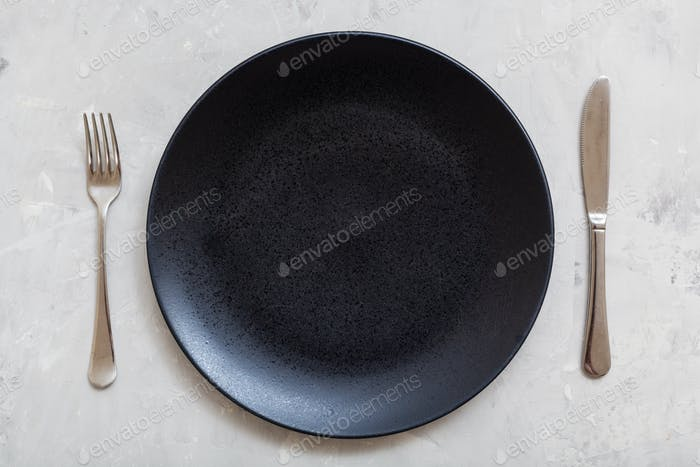 top view black plate with knife, spoon on concrete