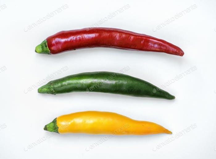 Aerial view of fresh red green yellow chili peppers on white bac