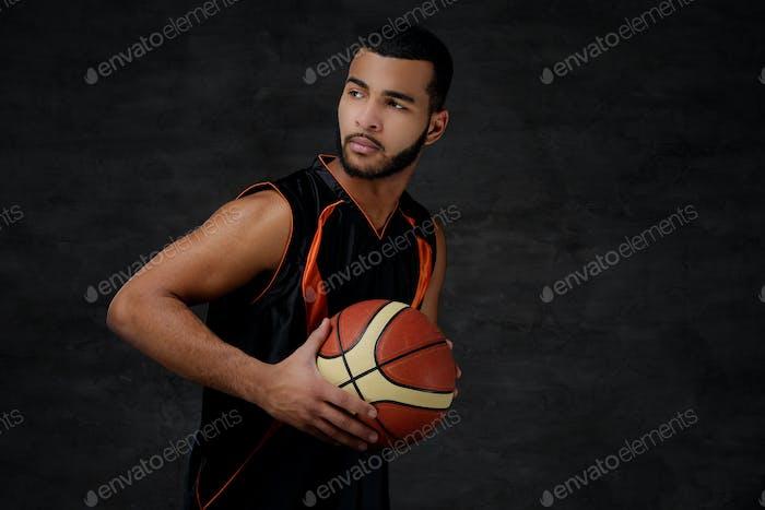 Young African-American basketball player in sportswear in a dark studio