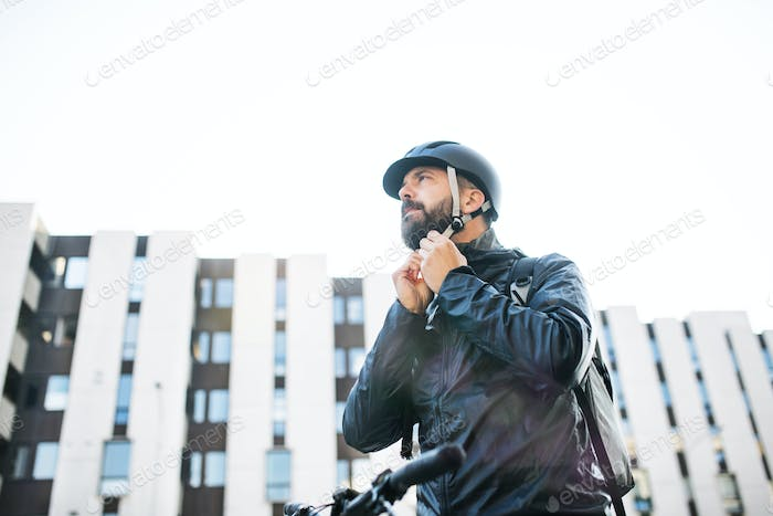Male courier with bicycle delivering packages in city, putting on a helmet.