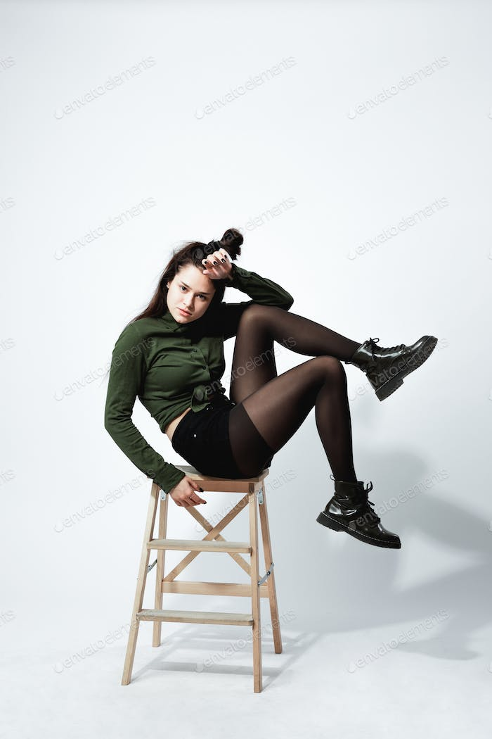 Stylish young dark-haired girl with a funny hairstyle dressed in green shirt, black shorts , tights