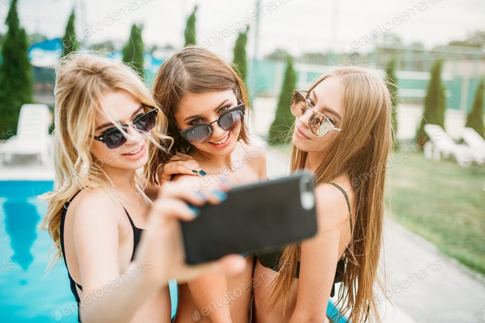 Three girls in swimsuits ad sunglasses make selfie