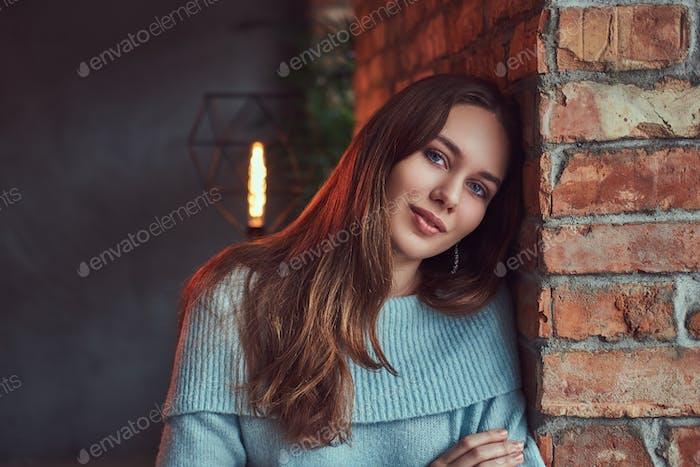 A sensual brunette in a gray sweater