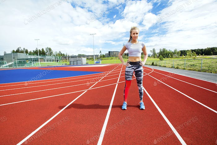 Sporty Woman Standing With Hands on Hips at Running Tracks