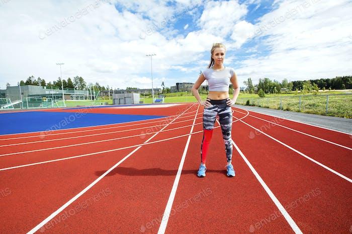 Sportliche Frau stehend mit Händen auf Hüften auf Laufstrecken