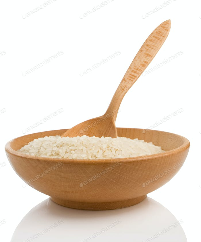 rice in plate and wooden spoon on white