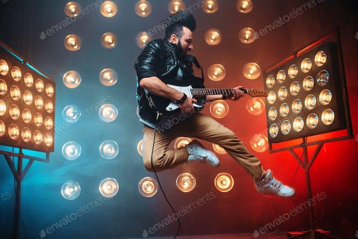 Männlicher Performer mit elektro- gitarre im Sprung