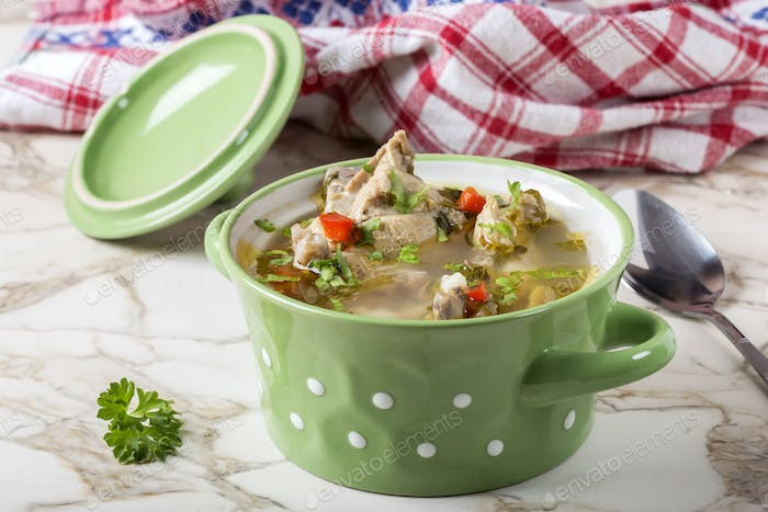 Homemade chicken soup in a green bowl