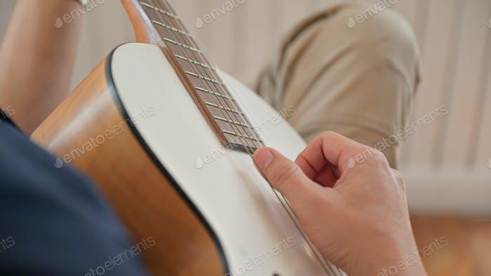 Junger Mann spielt Gitarre zu Hause Er hielt zu Hause wegen des Virenausbruchs.