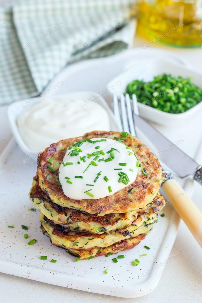 Vegetarische Zucchini-Krapfen oder Pfannkuchen, serviert mit griechischem Yogu