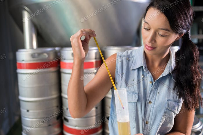 Worker examining beer in test tube at factory