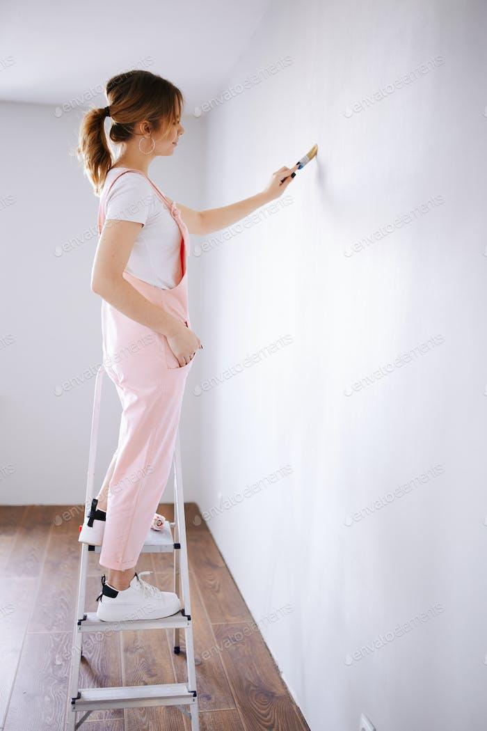 Das Mädchen macht Reparaturen in der Wohnung. Malen Sie die Wand und streichen Sie die Tür neu.