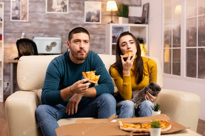 Gorgeous young couple eating pizza while watching TV