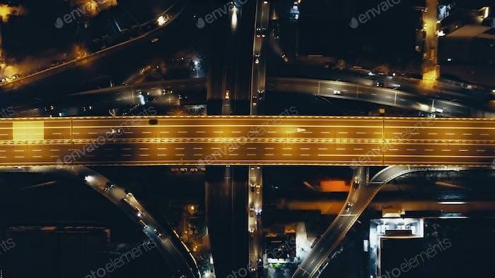 Top down night traffic highway bridge at Philippine metropolis city Manila. Aerial cars, truck drive