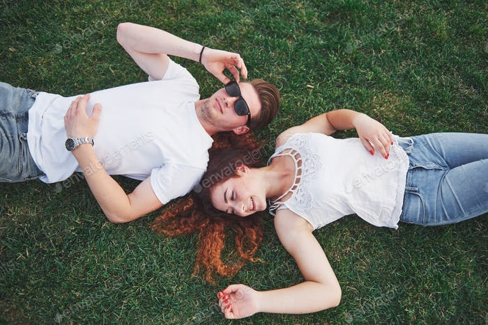 Cheerful couple lying on the grass. Young people outdoors. Happiness and harmony