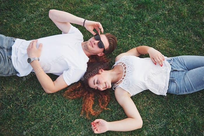 Fröhliches Paar auf dem Gras liegend. Junge Leute im Freien. Glück und Harmonie