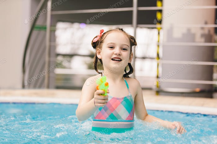 Little girl with water pistol in a swimming pool.