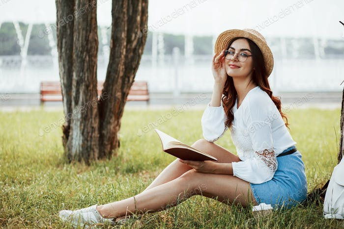 Leisure at free time. Young woman have weekend and sits in the park