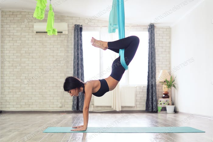 Adult woman practices anti-gravity yoga position in studio