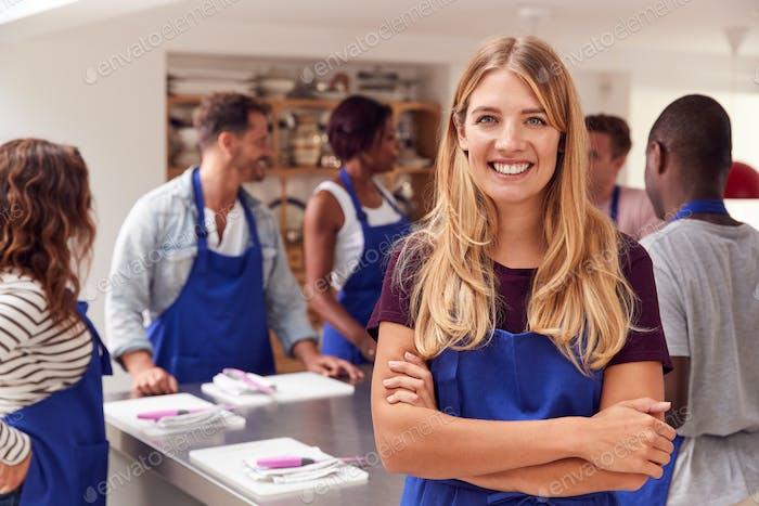 Porträt von Lächeln Frau Tragen Schürze Teilnahme an Kochkurs In Küche