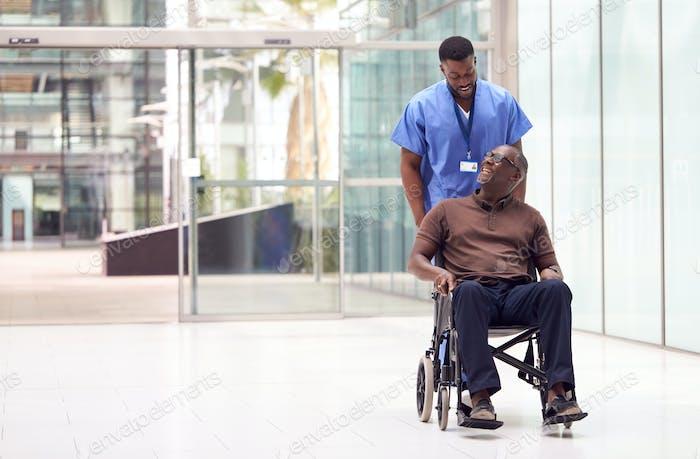 Männliche Krankenschwester Tragen Scrubs Wheeling Patient Im Rollstuhl Durch Lobby Der Moderne Krankenhaus Gebäude