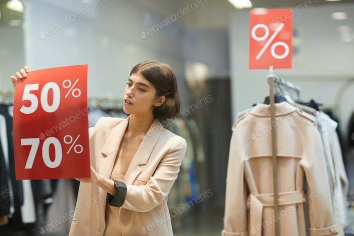 Woman Hanging Sale Signs in Store