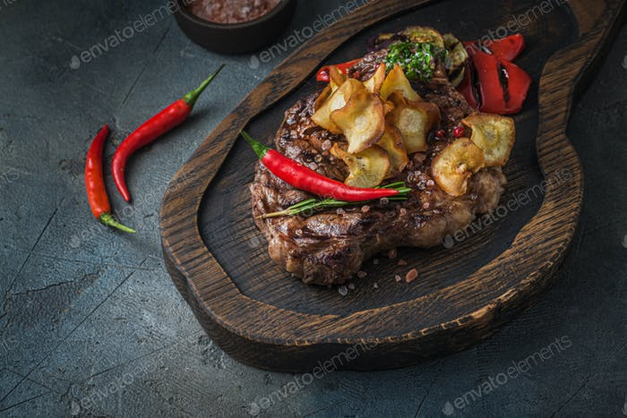 Juicy beef steak served on wooden board with crispy potatoe chips and chilli