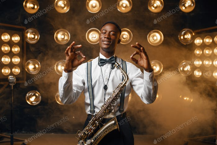 Black jazz performer with saxophone shows OK sign
