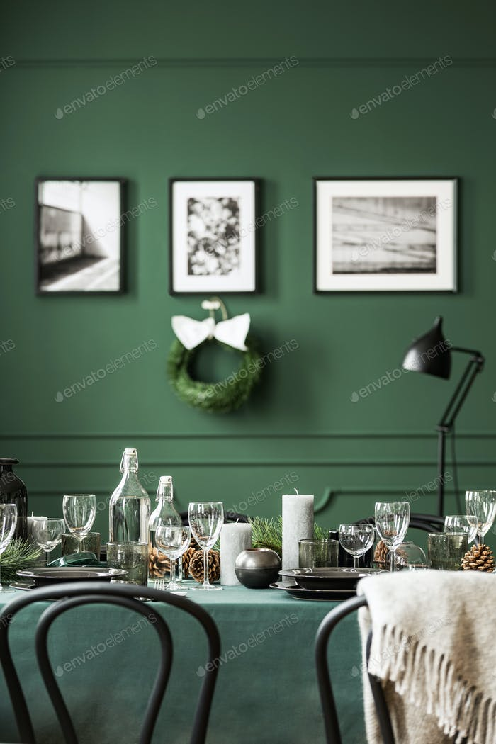 Wine glasses, candles and plates on table covered with green tab