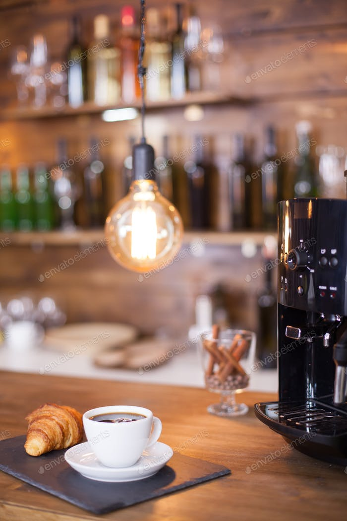 Modern coffee machine next to a cup of esoresso coffee on wooden counter bar