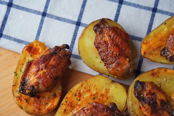 Baked chicken wings on potatoes