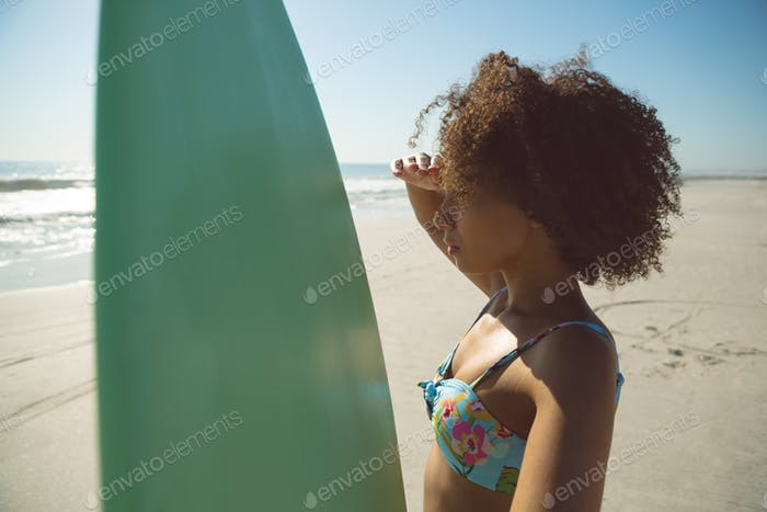 Side view of beautiful African american woman with surfboard shielding eyes at beach