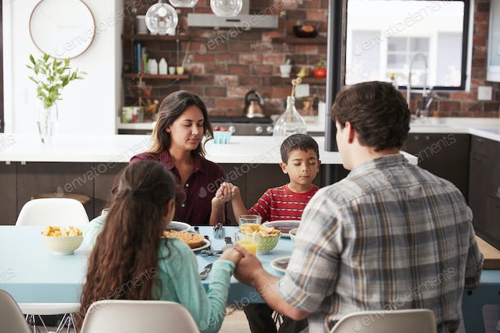 Family Praying Before Meal Around Table At Home