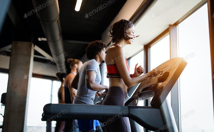 Фотография людей, бегущих на беговой дорожке в тренажерном зале
