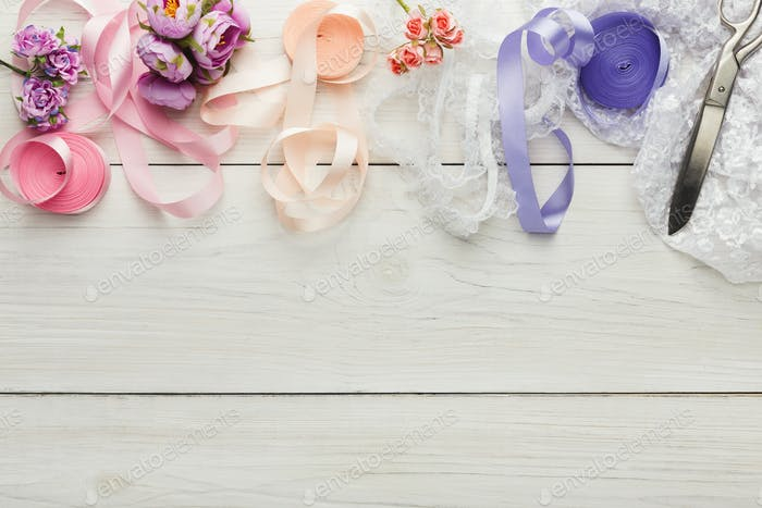 Colorful ribbons and garter on wooden table, wedding preparations background