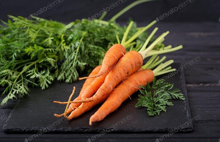 Bündel frische Karotten mit grünen Blättern auf dunklem Holzhintergrund.