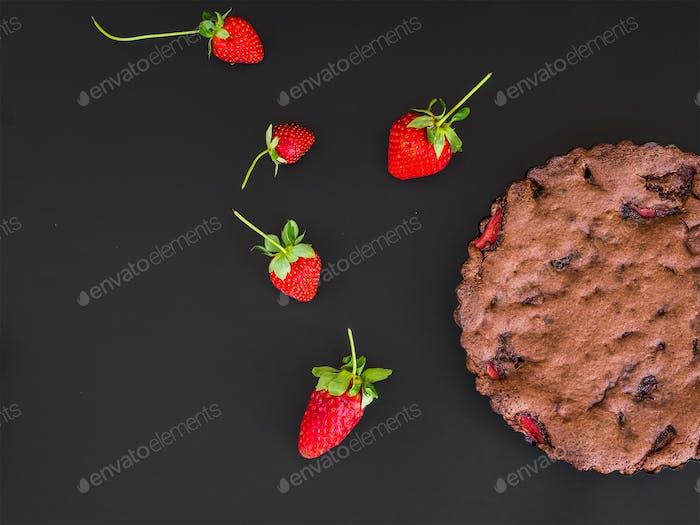 Chocolate strawberry cake with fresh strawberries on black
