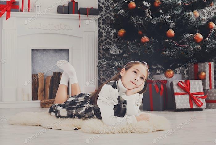 Schönes Kindermädchen und Weihnachtsgeschenk drinnen