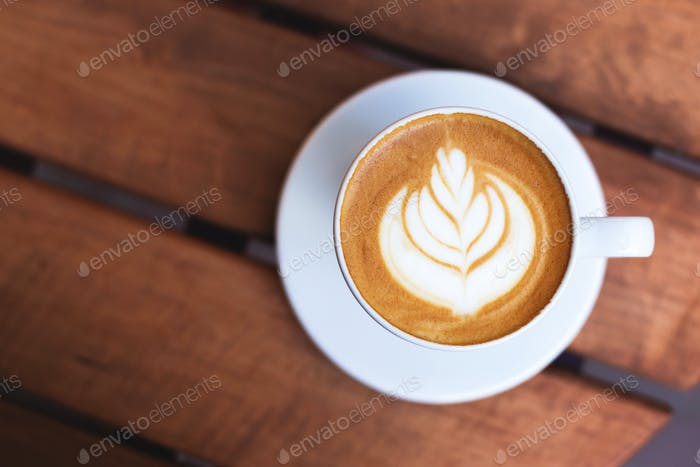 A Cup of Cappuccino with Latte Art on Wooden Table.