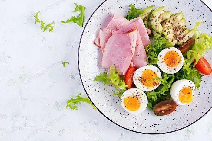 Ketogene/Paleo-Diät. Gekochte Eier, Schinken, Avocado und frischer Salat. Keto Frühstück.