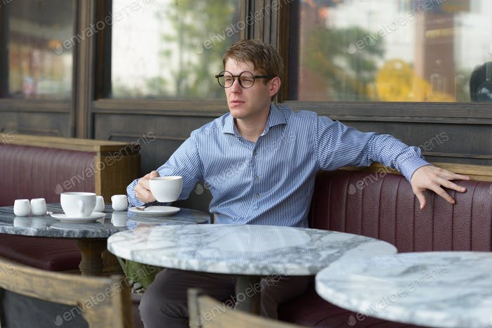 Young handsome blond businessman thinking at the coffee shop