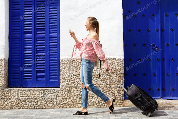 Full body young female traveler looking at mobile phone